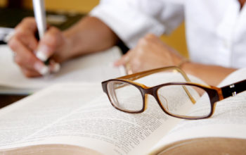 a woman's hand writing notes with eyeglasses on the book